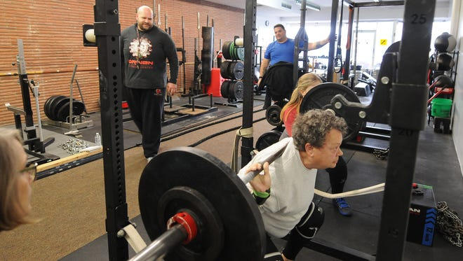 Scott Tully, left, watches as Sandy Wallace lefts squats as her friends Kathy Clark and Alex Usher spot her during her workout at Driven Fitness, 621 E Crawford Street, in Salina. Wallace at age 70 with 13 grandchildren can lift over 300 pounds and holds a record second in the nation for deadlifting 303 pounds in the drug tested division in the 70-74 age group.