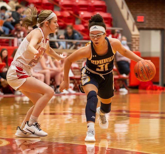 Stephenville's Mya Wesley (31) drives around Glen Rose's Zaidey Mills during action Tuesday night at Tiger Arena in Glen Rose.