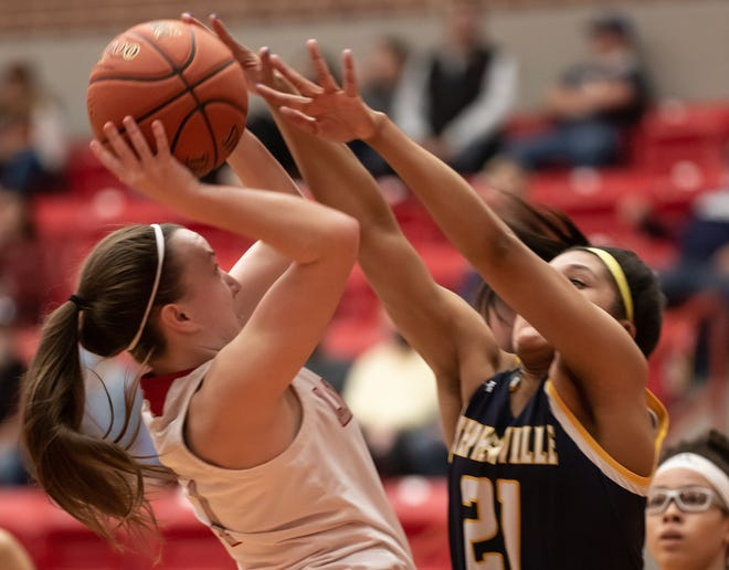 Stephenville's Alee McClendon (21) puts some pressure on Glen Rose's Hazel Hawkins as she takes the ball to the basket on Tuesday night. The Lady Tigers held off the Honeybees 39-33 in a big District 6-4A contest.