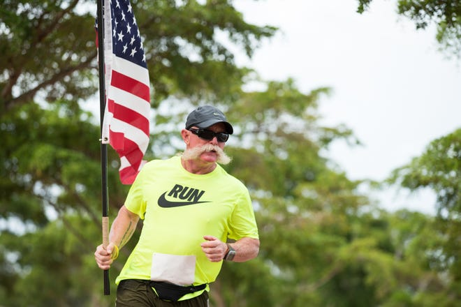 John Pyle runs a marathon carrying an American flag in the Random Acts of Giving (R.A.G.) lap race at Payne Park in downtown Sarasota, Fla., on Saturday November 9, 2013.