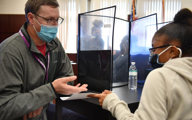 Booker High social studies teacher Ryan Kelley talks with junior Olivia Torres during class earlier this month. Face masks and the tri-fold desk shields are among the safety measures in place to mitigate the spread of COVID-19, although January was the worst month so far for the spread of the virus in Sarasota schools. [Herald-Tribune staff photo/Mike Lang]