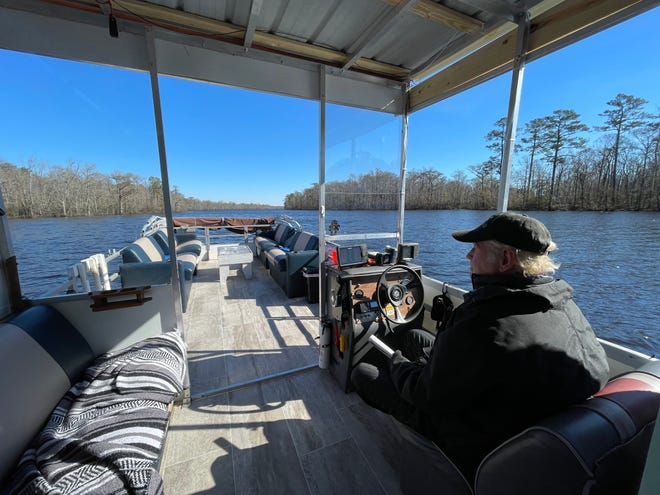Doug Springer sits behind the wheel of a 1986 pontoon boat he has outfitted to give tours of the often-forgotten Northeast Cape Fear River, through his new business Castle Hayne Water Tours.