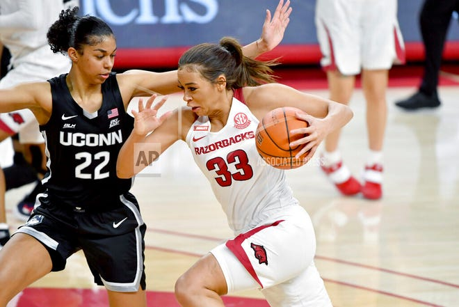 Arkansas guard Chelsea Dungee (33) tries to drive past Connecticut defender Evina Westbrook (22) during the first half of an NCAA college basketball game Thursday, Jan. 28, 2021, in Fayetteville, Ark.