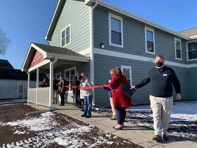 Chris Palmer, right, executive director of Cornerstone of Topeka, gestures toward fellow Cornerstone members and city of Topeka personnel as they prepare to cut the ribbon Friday morning on several new affordable housing units in central Topeka.