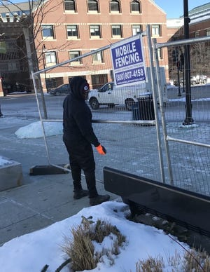 "Paul Richard, of Mobile Fencing, considered the single-digits temps ""not that bad."" He installed temporary fencing at the Mercantile Center Friday morning in Worcester."