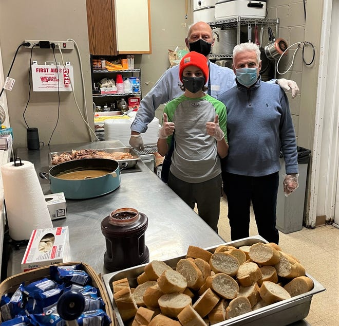 The Clinton Rotary Club continues to make turkey dinners 'to go' at the WHEAT Community Cafe. Helping out recently are Darrell Wickman (back), John Schmidt (right) and 15-year-old Bobby Williams. doing their part during the pandemic.