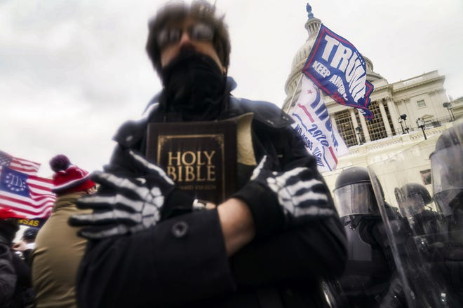 A man holds a Bible as, Trump supporters gather Jan. 6 outside the Capitol in Washington, D.C.