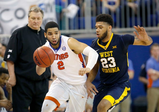 Florida guard Brandone Francis-Ramirez dribbles up the court past West Virginia forward Esa Ahmad (23) and head coach Bob Huggins during the second half of the Jan. 30, 2016 game at the O'Connell Center. Florida defeated West Virginia 88-71.