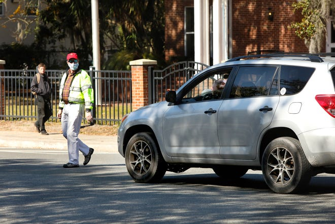 A motorist yells at assistant chief Terry Pierce, with the Gainesville Police Department, as he walks across traffic on University Avenue during the start of Operation Gator Steps by the City of Gainesville, the Gainesville Police Department, UF and the UF Police Department off West University Avenue. The operation, which will last about 30 days to start off, involves law enforcement using aggressive tactics to catch motorists that are not yielding right of way to pedestrians. The operation is in response to the recent deaths of two University of Florida students in crashes near campus.
