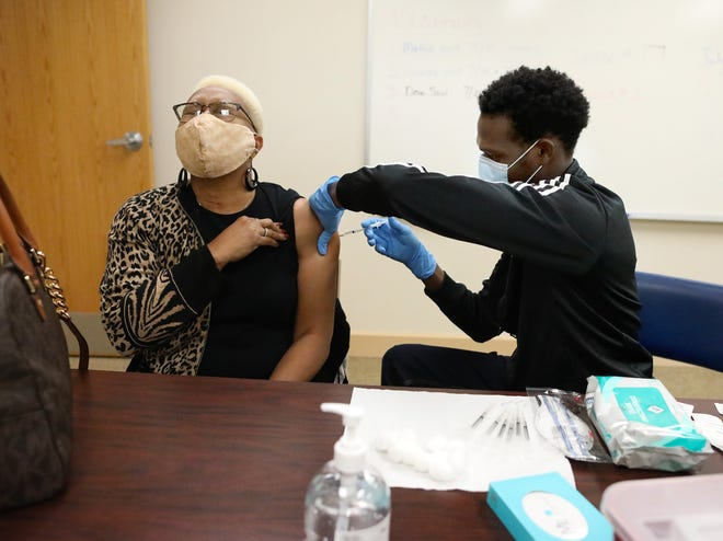 """Gwen Tillman-Williams closes her eyes and says """"Thank you, Jesus,"""" as she gets the first dose of a Pfizer COVID-19 vaccination from Dr. Etzer Augustine, a surgical resident at UF Health, during a vaccination session at Tillman-Williams' church Mount Moriah Missionary Baptist Church in Gainesville."""