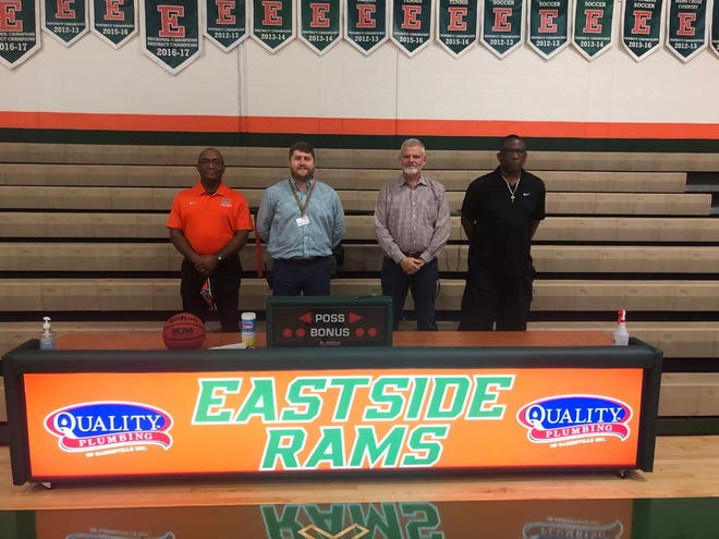 """Bryan Nazworth, owner and founder of Quality Plumbing, second from right, donated a new scoring table to the Eastside High School athletic program. Standing with Nazworth are, from left, girls basketball coach Mark Hickman, athletic director Phillip Crutchfield, and boys basketball coach Herman """"Pop"""" Williams."""