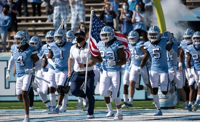 North Carolina players, led by defensive back Trey Morrison, left, and running back Josh Henderson, carrying the flag, take the field prior to a November victory against Wake Forest at Kenan Stadium in Chapel Hill.