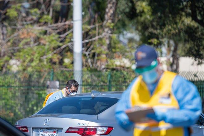 San Bernardino County public health workers screen drivers during a drive-thru COVID-19 testing event in San Bernardino on Friday, March 27, 2020.