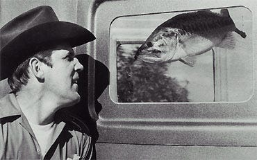 """Bill Sargent shot this photo of Ray Scott and a bass going eye-to-eye at the 1972 Florida National tournament on the Kissimmee Chain of Lakes when BASS introduced its """"Don't Kill Your Catch"""" program."""