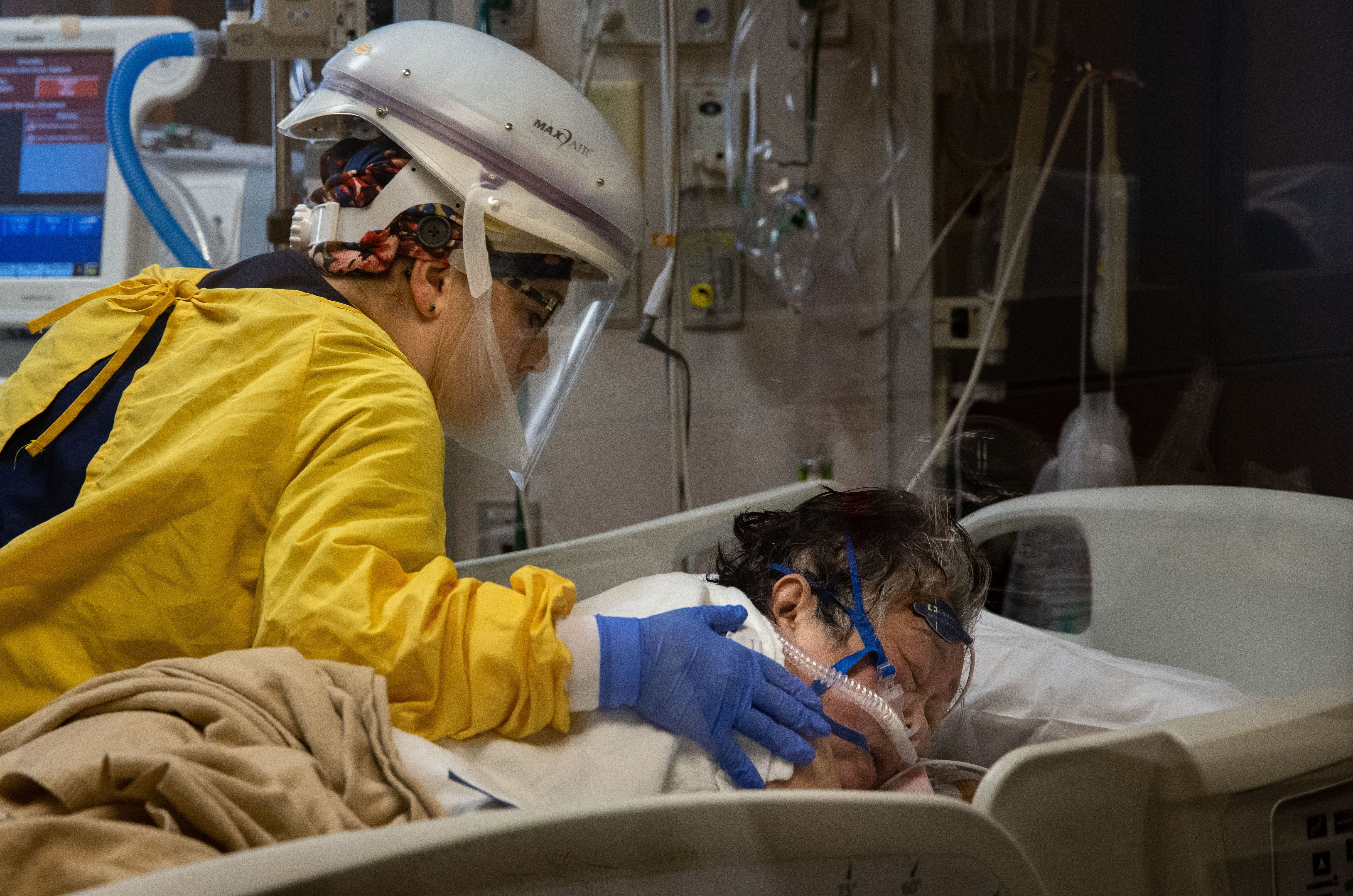 ICU nurse Monica Bohnert rubs Thong Sengphirom's back as she rests in a prone position to help her breathe on Dec. 10.