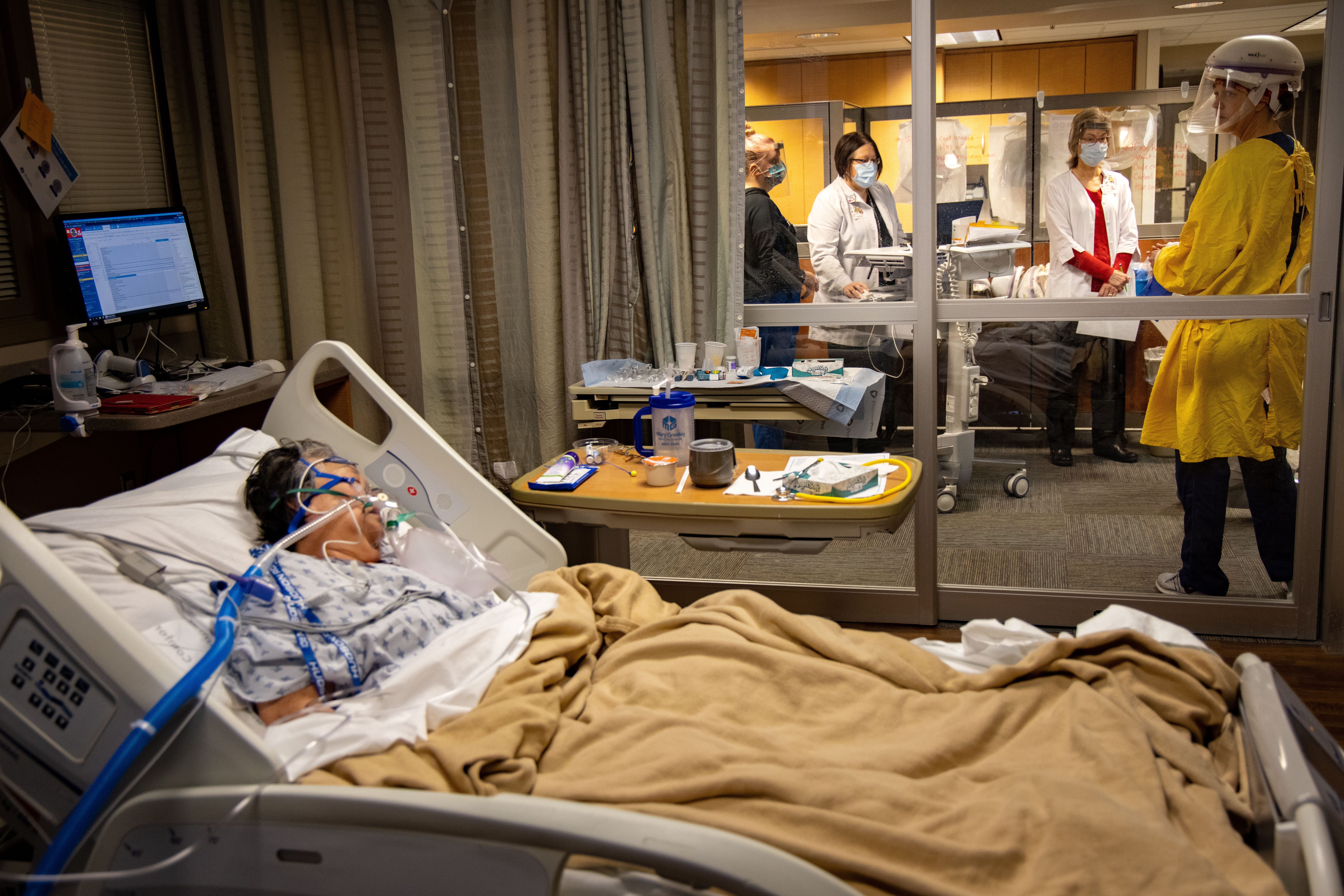 ICU staff discuss care options for COVID-19 patient Thong Sengphirom during morning rounds at Mary Greeley Medical Center in Ames, Friday, Dec. 11, 2020.