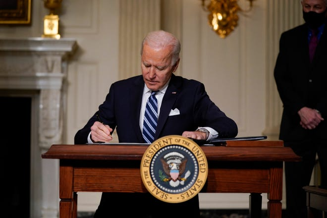 President Joe Biden signs an executive order on climate change, in the State Dining Room of the White House on Jan. 27, 2021, in Washington.