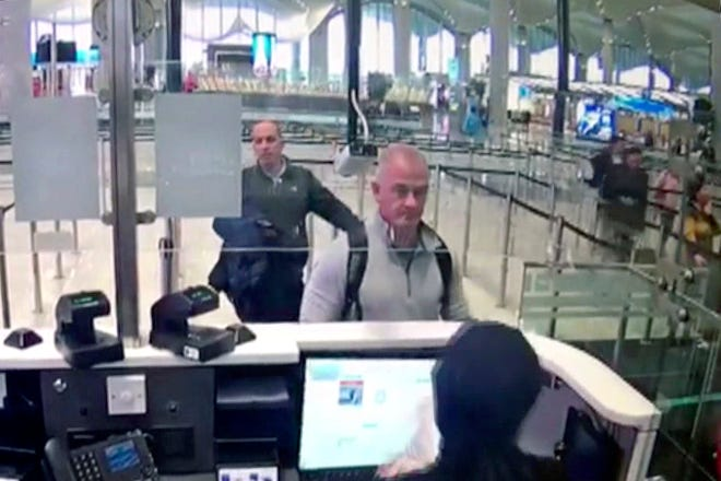 FILE - This Dec. 30, 2019 image from security camera video shows Michael L. Taylor, center, and George-Antoine Zayek at passport control at Istanbul Airport in Turkey.