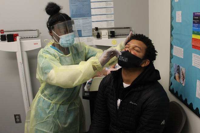 Joanicha Pryor, a medical assisting student at Terra State Community College, conducts a COVID-19 test on Duane Satchell, a member of the college's men's basketball team, Thursday at one of the medical assisting department's exam rooms. Terra State will begin offering COVID-19 antibody tests through its medical assisting department in February.