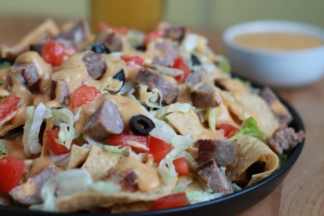 Nachos take on a Wisconsin flavor when topped with bratwurst and a homemade beer cheese sauce.