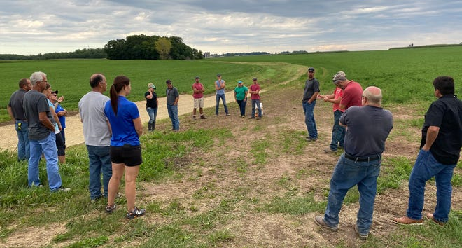 Participants in a Peninsula Pride Farms Conservation Conversation field event discuss the benefits of grass waterways, one of the practices farmers can use to help slow soil erosion and runoff.