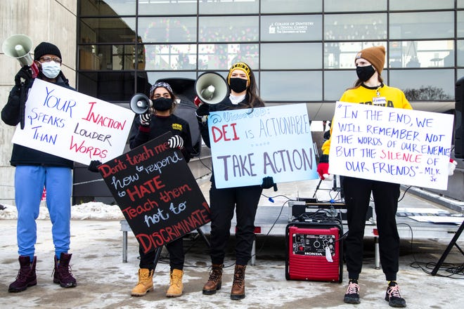 """University of Iowa dental students, from left, AJ Foley, Megha Puranam, Jasmine Butler, and Shannon Oslad, hold signs and chant during a protest organized by Action UIowa Task Force to, """"Put DEI in DDS,"""" Friday, Jan. 29, 2021, outside the College of Dentistry on the University of Iowa campus in Iowa City, Iowa."""