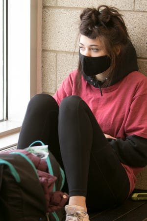 Brighton High School freshman Hailey Watson waits for her parents to pick her up from school Thursday, Jan. 28, 2021, wearing a required face mask.