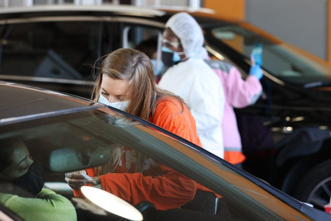 Claire Thomas, a pharmacy student at UTHSC, administers COVID-19 vaccines while volunteering for the Shelby County Health Department at the site of the former Appling Emissions Station on Friday, Jan. 29, 2021.