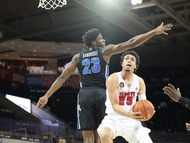 Malcolm Dandridge goes for a block defending SMU's Ethan Chargois in the Tigers' game at SMU on Thursday Jan. 28, 2021.