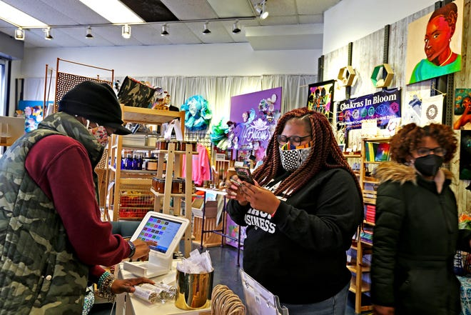 Tamira White, left, owner of Distinctive Designs, checks out customer Brit Nicole, center, who was shopping at the Bronzeville Collective at 339 W. North Ave. on Thursday. The Bronzeville Collective shares space with 26 artists and business owners of color and is among the newer businesses near the south end of King Drive.