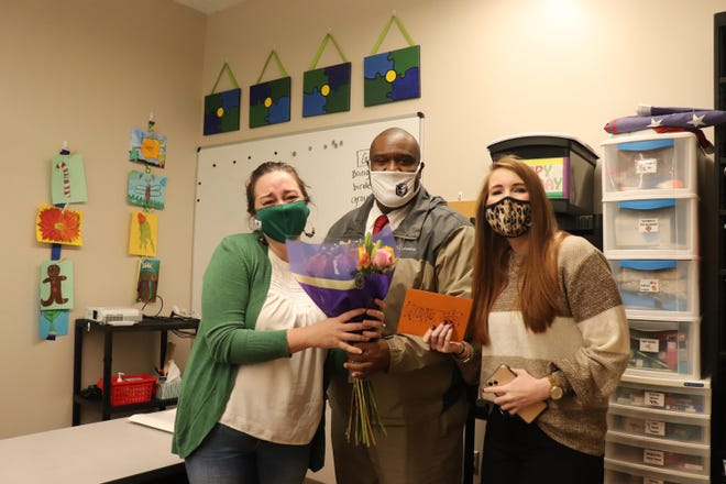 Pike Road High School special education teacher Erica Dunwoody, left, is presented with flowers from PRHS Principal Greg Foster, and assistant principal Brittney Duncan. Dunwoody was recognized for her selection as teacher of the year.