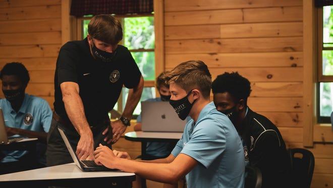 El coordinador del aula de fútbol de la ciudad de Málaga, Craig Canavan, da instrucciones a un alumno de un internado.