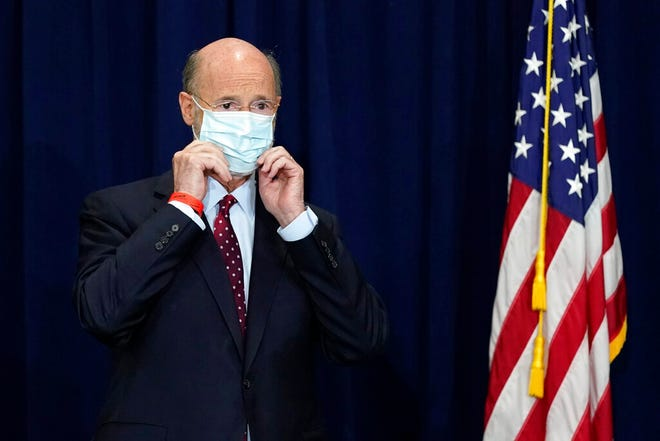 FILE - In this Nov. 4, 2020, file photo, Pennsylvania Gov. Tom Wolf adjusts his face mask to protect against COVID-19 during a news conference in Harrisburg, Pa., regarding the counting of ballots in the 2020 general election. Facing a deep, pandemic-inflicted budget deficit, Gov. Wolf will ask lawmakers for billions of dollars funded by higher taxes on Pennsylvania's huge natural gas industry for workforce development and employment assistance to help the state recover. (AP Photo/Julio Cortez, File)