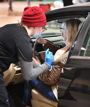 In this file photo, Kelsey Enlow, a physicians assistant student, administers a Pfizer vaccine injection during a Community Healthcare Center drive-thru vaccination clinic. The Community Healthcare Center will be hosting two Moderna COVID-19 vaccine clinics Thursday, May 6, in Wichita Falls and Burkburnett.
