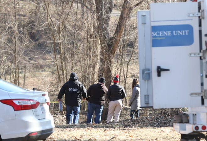 A Bureau of Criminal Investigation agent carries supplies toward the scene where human remains were found in Chaps Run Park in Zanesville on Friday.