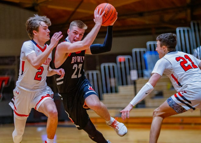 Bowie Bulldogs guard Coleton Benson drives the ball to the basket between Lake Travis Cavaliers guard Jake Stephens, left, and guard Cash Clayton at the District 26-6A boys basketball game on Jan. 29 at Lake Travis High School. Benson scored 42 points to lead Bowie to the 75-58 win.
