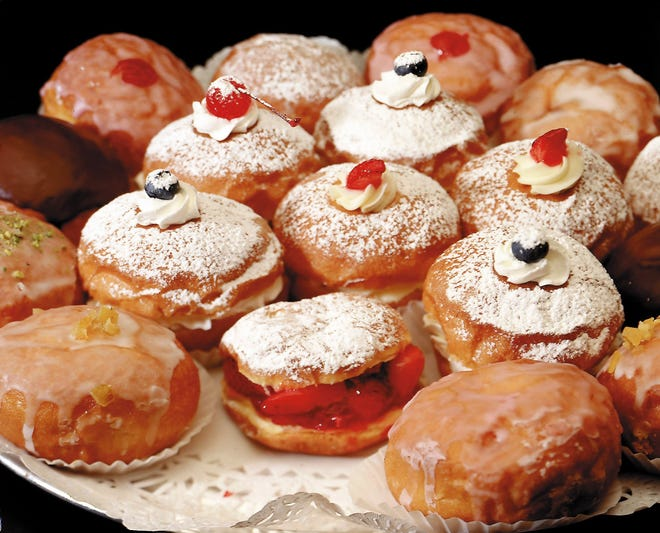 Traditional Polish paczki are filled with fruit and jam at a bakery near Chicago.