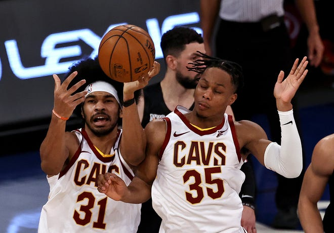 Cavaliers' Jarrett Allen, left, and Isaac Okoro go after a loose ball in the fourth quarter against the New York Knicks during an NBA basketball game Friday, Jan. 29, 2021, in New York. (Elsa/Pool Photo via AP)