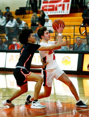 Ashland's Luke Denbow (4) drives to the rim as Massillon Washington's Lavarion Moore (5) defends during the Arrows' 56-53 win Friday at Arrow Arena.