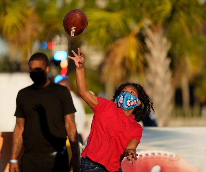 Anaja Brackett throws a pass at the NFL Experience for Super Bowl LV on Friday in Tampa, Fla.