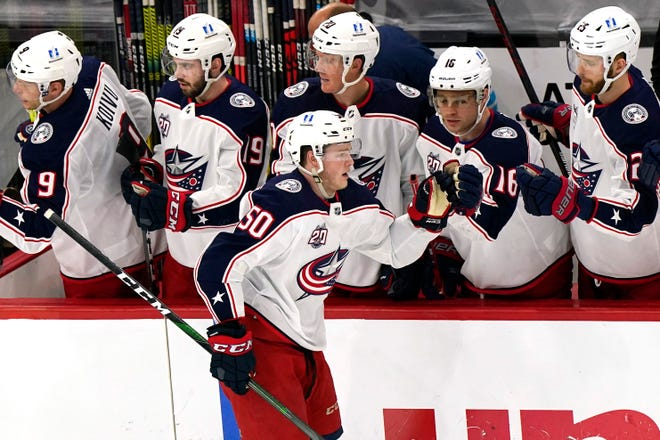 Eric Robinson celebrates with his Blue Jackets teammates after scoring against the Blackhawks on Friday.