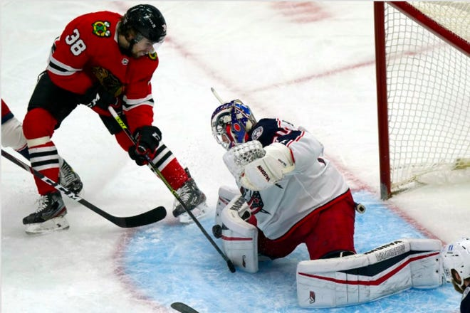 Joonas Korpisalo, right, makes a save against the Chicago Blackhawks' Brandon Hagel in the second period of the Blue Jackets' 2-1 victory Friday night in Chicago. (AP Photo/Nam Y. Huh)