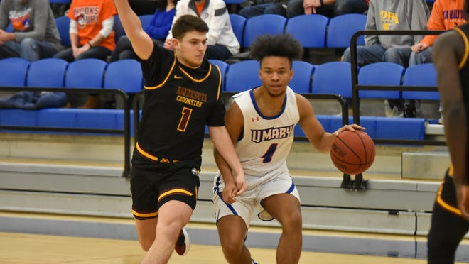 Georges Darwiche defends UMary's Glenn Jordan during Friday's game between Minnesota Crookston and UMary in Bismarck. Darwiche dished out eight assists in the Golden Eagles, 72-58 win.