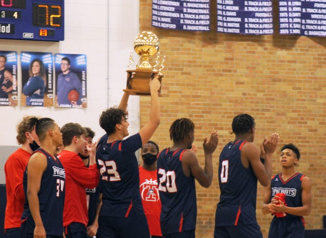 Truman senior Runey Hernandez (23) hoists the Three Trails Trophy as the Patriots celebrate a 72-45 victory over William Chrisman Friday night. Truman kept the trophy given out to the winner of the annual Noland Road rivalry game.