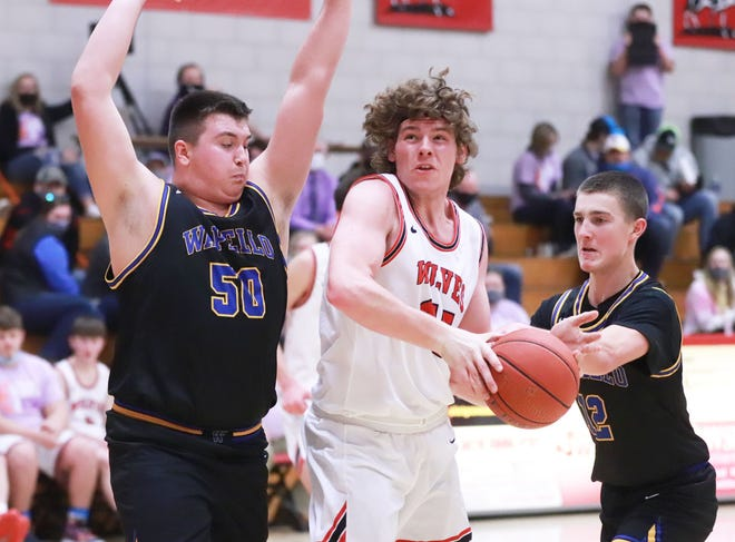 Winfield-Mt. Union's Bryce Wade goes to the hoop guarded by Wapello's Rhett Smith (left) and Tade Parsons (right) on Friday night at Winfield.