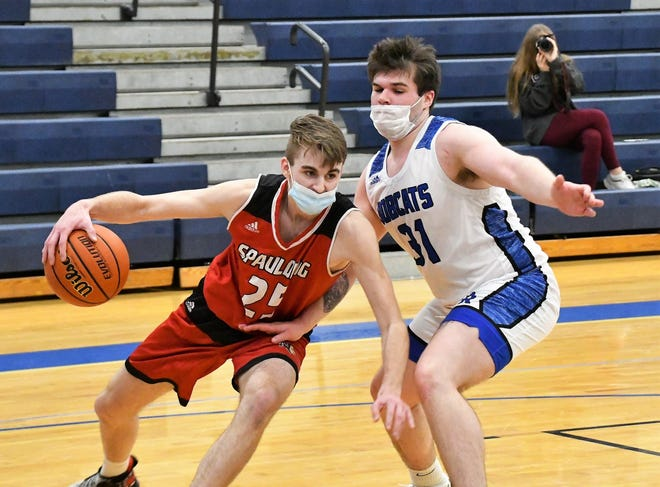 Spaulding's Mark Frost, left, tries to maneuver past Oyster River's Doug MacGown on Friday night in Durham. Frost had 14 points and 15 boards in the 47-45 victory.