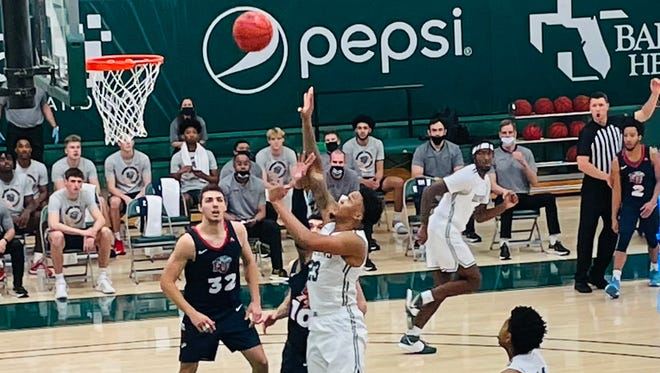 Jacksonville University's Tyreese Davis shoots over Liberty's Elijah Cuffee (10) during Friday's ASUN game at Swisher Gym.