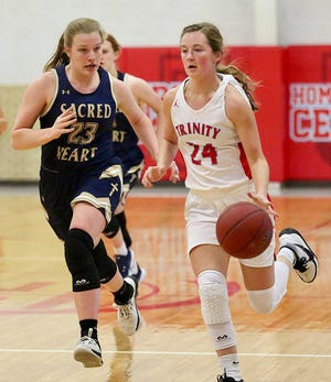 Trinity Catholic's Hayley Hughes (24) drives down the court past Sacred Heart's Teghan Slagle (23) during their game Friday night in Hutchinson. Hughes scored 27 points in the game. Trinity defeated Sacred Heart 47-39.