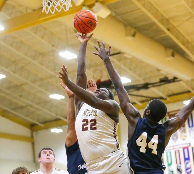 Stow-Munroe Falls forward Desmond Copeland splits a pair of Twinsburg defenders during the Bulldogs' 37-36 overtime win over the Tigers Friday at home. Copeland led all scorers with 15 points.