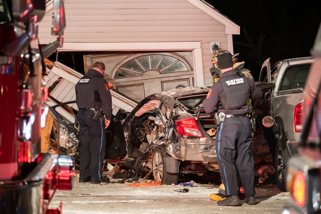 A Natick police officer looks over the scene of the accident at 148 Hartford St., Jan. 29, 2021. The driver and passenger suffered serious injuries in the 10:30 p.m. crash.